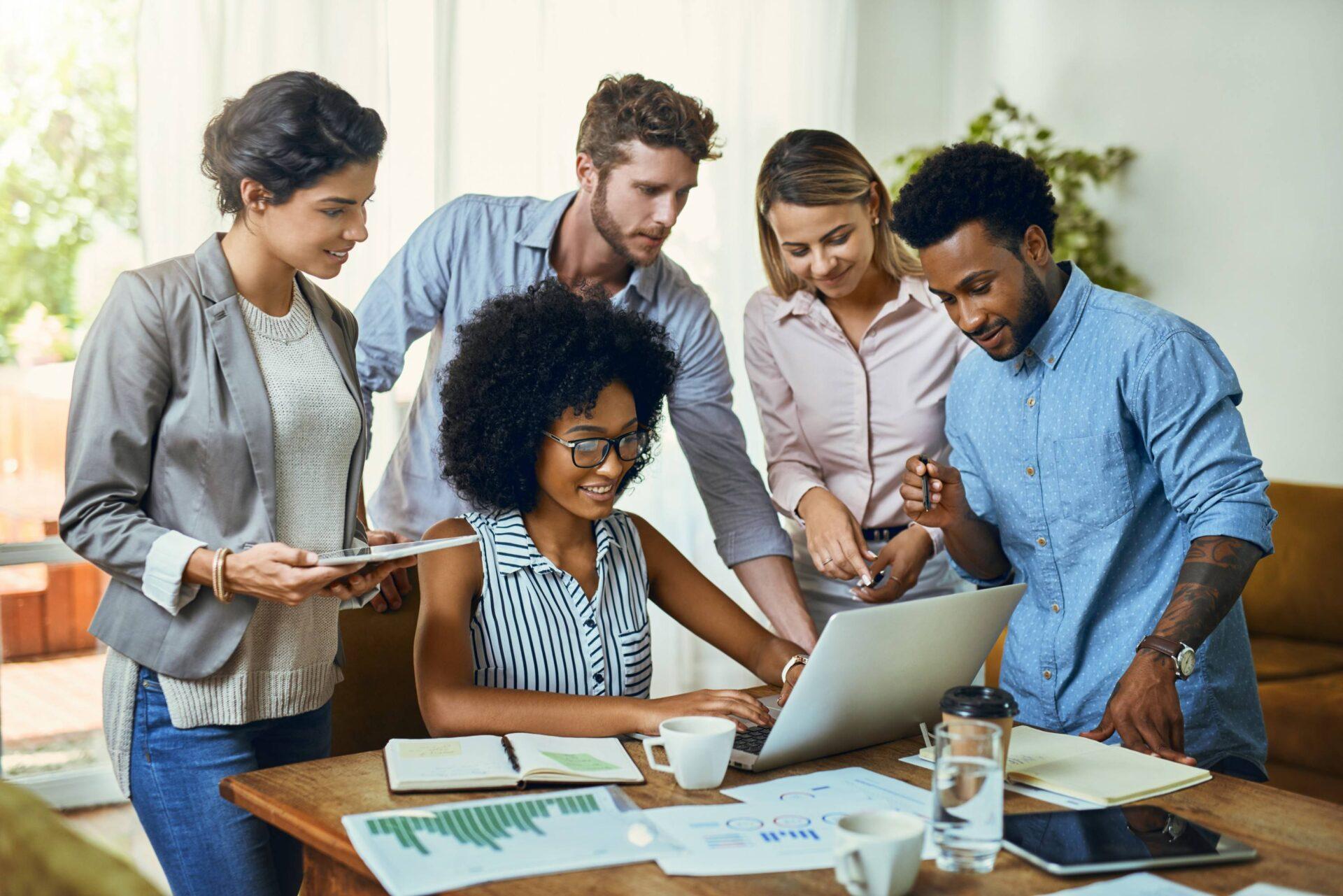 Pessoas olhando um computador ao redor de uma mesa